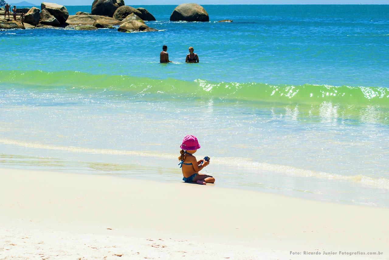 Foto de uma criança brincando na areia e ao fundo um mar clarinho da Praia de Bombinhas - Santa Catarina – Fotos de Ricardo Junior / www.ricardojuniorfotografias.com.br